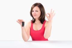 La giovane donna felice sta tenendo le chiavi dell'automobile e sta mostrando il gesto giusto Fotografie Stock Libere da Diritti