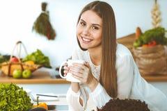 La giovane donna felice sta tenendo la tazza bianca e sta esaminando la macchina fotografica mentre si sedeva alla tavola di legn fotografia stock libera da diritti