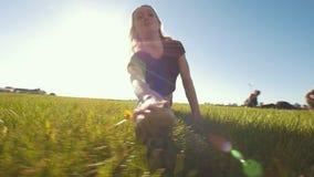 La giovane donna flessibile ha allungato sulla cordicella sull'erba nel giorno di estate video d archivio