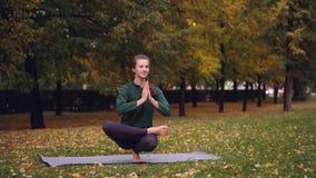 La giovane donna flessibile sta equilibrando su un piede che si tiene per mano nel namaste che gode di singola pratica in parco B video d archivio