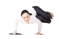 La giovane donna in formalwear che fa la forma fisica si esercita con il libro su w Immagini Stock Libere da Diritti