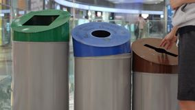 La giovane donna getta i rifiuti nel bidone della spazzatura Separazione e riciclaggio residui Movimento lento video d archivio