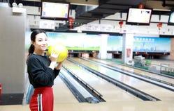 La giovane donna gioca il bowling immagine stock libera da diritti