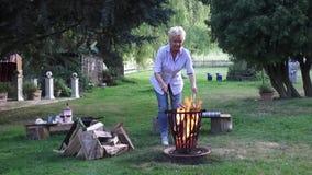 La giovane donna gode della sera romantica dal fuoco di accampamento e griglia le salsiccie stock footage