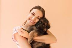 La giovane donna gode di di abbracciare un piccolo cucciolo sveglio fotografie stock libere da diritti