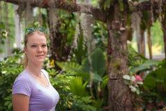 La giovane donna gode di bei fiori in giardino tropicale Immagini Stock