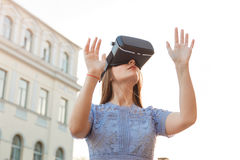 La giovane donna gode di con il dispositivo di VR all'aperto fotografia stock libera da diritti