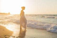 La giovane donna gode di di camminare su una spiaggia nebbiosa al crepuscolo Fotografia Stock Libera da Diritti