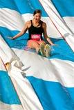 La giovane donna gode di di scendere lo scorrevole nella corsa di ostacolo Fotografie Stock Libere da Diritti