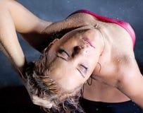 La giovane donna gode di nelle goccioline di acqua fotografie stock libere da diritti
