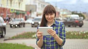 La giovane donna gode di una compressa digitale accanto ad una strada di grande traffico archivi video