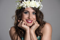 La giovane donna graziosa affascinante con la testa in mani posa sorridere e l'esame della macchina fotografica Fotografia Stock