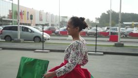La giovane donna graziosa castana in bello vestito con i sacchetti della spesa va sulla via al rallentatore 1920x1080 stock footage