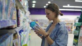 La giovane donna graziosa in casuale esamina le merci in un supermercato Legge l'etichetta sul prodotto Seleziona un risciacquo d archivi video