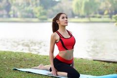 La giovane donna graziosa che fa l'yoga si esercita in parco Immagini Stock