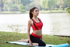 La giovane donna graziosa che fa l'yoga si esercita in parco Immagine Stock Libera da Diritti