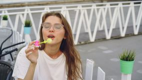 La giovane donna graziosa che indossa gli occhiali da sole sta soffiando le bolle di sapone che si siedono all'aperto e che sorri archivi video
