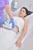 La giovane donna graziosa che ottiene a cryolipolyse il trattamento grasso dentro professa Fotografie Stock Libere da Diritti