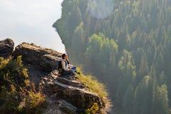 La giovane donna graziosa che si siede sopra la montagna, si rilassa, calma e meditazione con la natura immagine stock