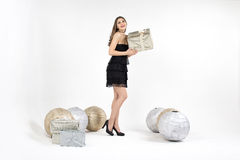 La giovane donna graziosa con la scatola e le decorazioni attuali dorate sorride Fotografia Stock