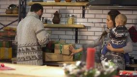 La giovane donna graziosa con un bambino nelle sue armi e l'uomo barbuto in maglione caldo distinguono i regali presenta le scato stock footage