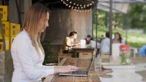 La giovane donna graziosa di affari che per mezzo del computer portatile su pranzo irrompe un caffè all'aperto archivi video
