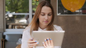 La giovane donna graziosa di affari che per mezzo del PC della compressa su pranzo irrompe un caffè all'aperto archivi video