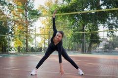 La giovane donna graziosa di forma fisica fa l'allungamento degli esercizi durante il lavoro Immagine Stock Libera da Diritti
