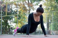 La giovane donna graziosa di forma fisica fa l'allungamento degli esercizi durante il trai Immagini Stock