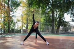 La giovane donna graziosa di forma fisica fa l'allungamento degli esercizi durante il trai Immagini Stock Libere da Diritti