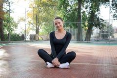 La giovane donna graziosa di forma fisica fa l'allungamento degli esercizi durante lo spor Fotografie Stock Libere da Diritti
