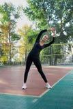 La giovane donna graziosa di forma fisica fa l'allungamento degli esercizi durante lo spor Immagini Stock