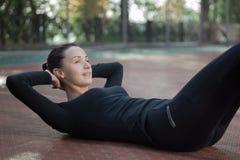 La giovane donna graziosa di forma fisica si esercita durante il traini di sport di mattina Immagine Stock Libera da Diritti