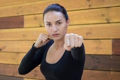La giovane donna graziosa di forma fisica si esercita durante l'allenamento di pugilato Immagine Stock