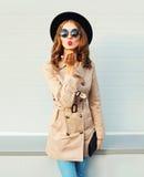 La giovane donna graziosa di modo che soffia le labbra rosse invia il bacio dolce che porta un cappotto black hat degli occhiali  Immagini Stock