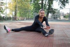 La giovane donna graziosa fa l'allungamento degli esercizi durante il traini di sport Immagine Stock