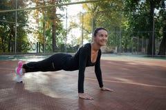 La giovane donna graziosa fa l'allungamento degli esercizi durante l'addestramento sopra Immagine Stock Libera da Diritti