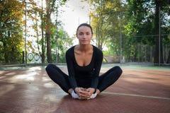 La giovane donna graziosa fa l'allungamento degli esercizi durante l'allenamento sulla p Immagine Stock Libera da Diritti