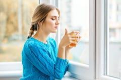 La giovane donna graziosa guarda dalla finestra e beve il tè L'ufficio della C Immagini Stock Libere da Diritti