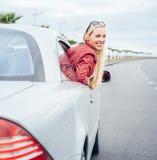 La giovane donna graziosa guarda fuori dall'automobile Fotografia Stock