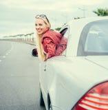 La giovane donna graziosa guarda fuori dall'automobile Immagini Stock Libere da Diritti
