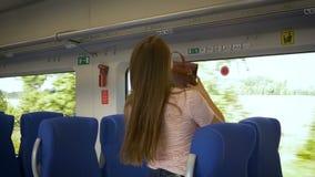 La giovane donna graziosa mette i bagagli nel vagone video d archivio