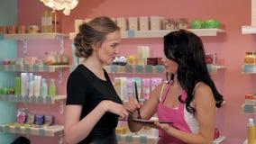 La giovane donna graziosa nel negozio della profumeria sceglie i cosmetici con cosultant Immagine Stock