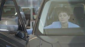 La giovane donna graziosa nel vestito blu di usura convenzionale apre la porta dell'automobile e si siede dentro nel salone dell' stock footage