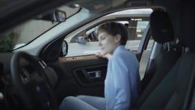 La giovane donna graziosa nel vestito blu di usura convenzionale apre la porta dell'automobile e si siede dentro nel sedile del p video d archivio