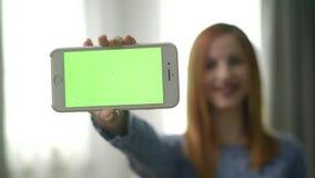 La giovane donna graziosa nella sala mostra che il dispositivo con greenscreen video d archivio