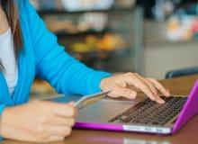 La giovane donna graziosa passa la tenuta della carta di credito e per mezzo del computer portatile Immagini Stock Libere da Diritti