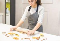 La giovane donna graziosa prepara la pasta e cuoce il pan di zenzero ed i biscotti nella cucina Buon Natale e nuovo felice fotografia stock