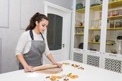 La giovane donna graziosa prepara la pasta e cuoce il pan di zenzero ed i biscotti nella cucina Buon Natale e nuovo felice immagine stock