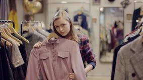 La giovane donna graziosa prova sopra un vestito e esaminare la macchina fotografica in un negozio di vestiti archivi video